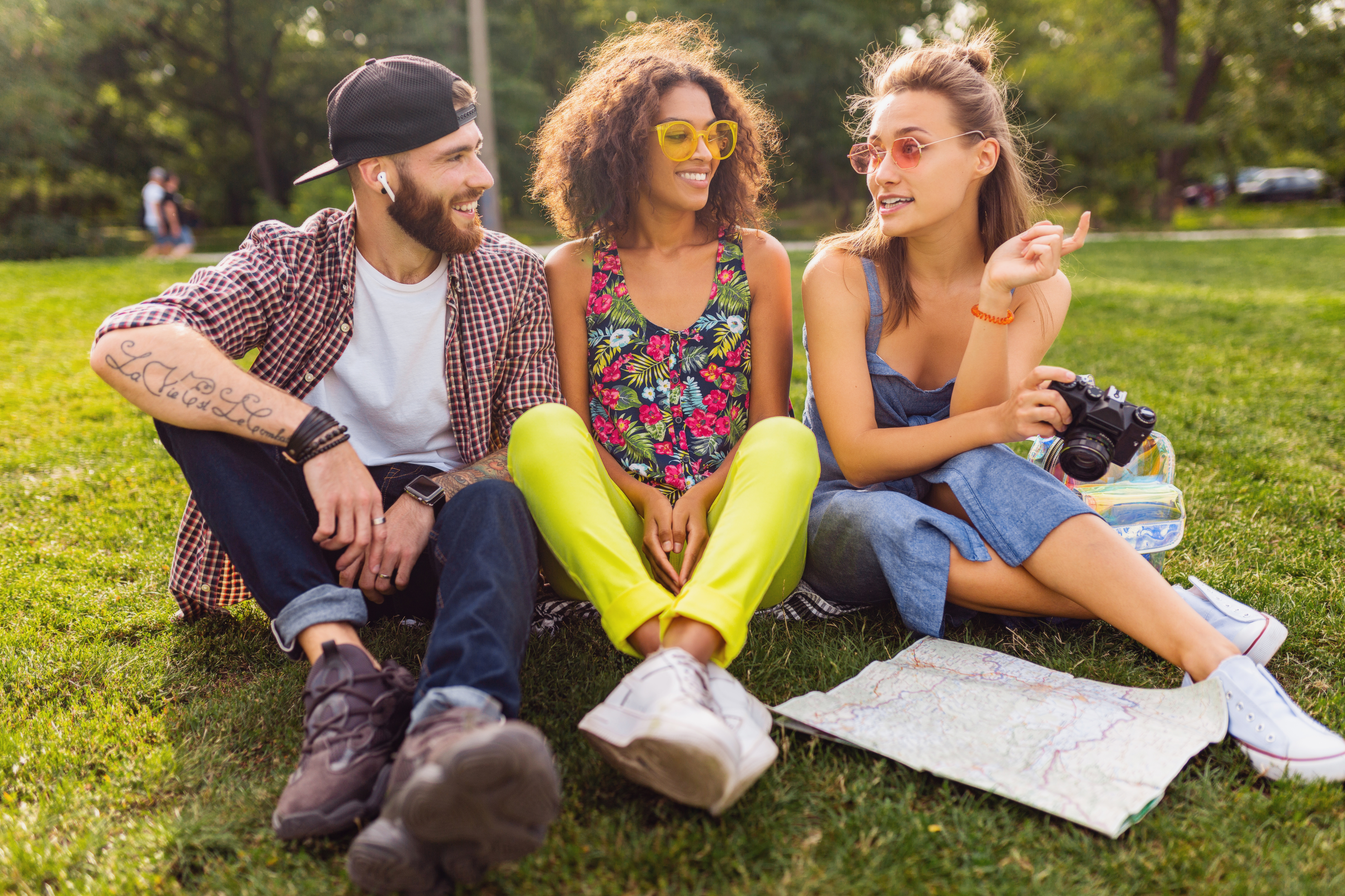 happy-young-company-friends-sitting-park-traveling-looking-map-sightseeing-man-women-having-fun-together-colorful-summer-hipster-fashion-style-taking-photo-camera-talking-smiling