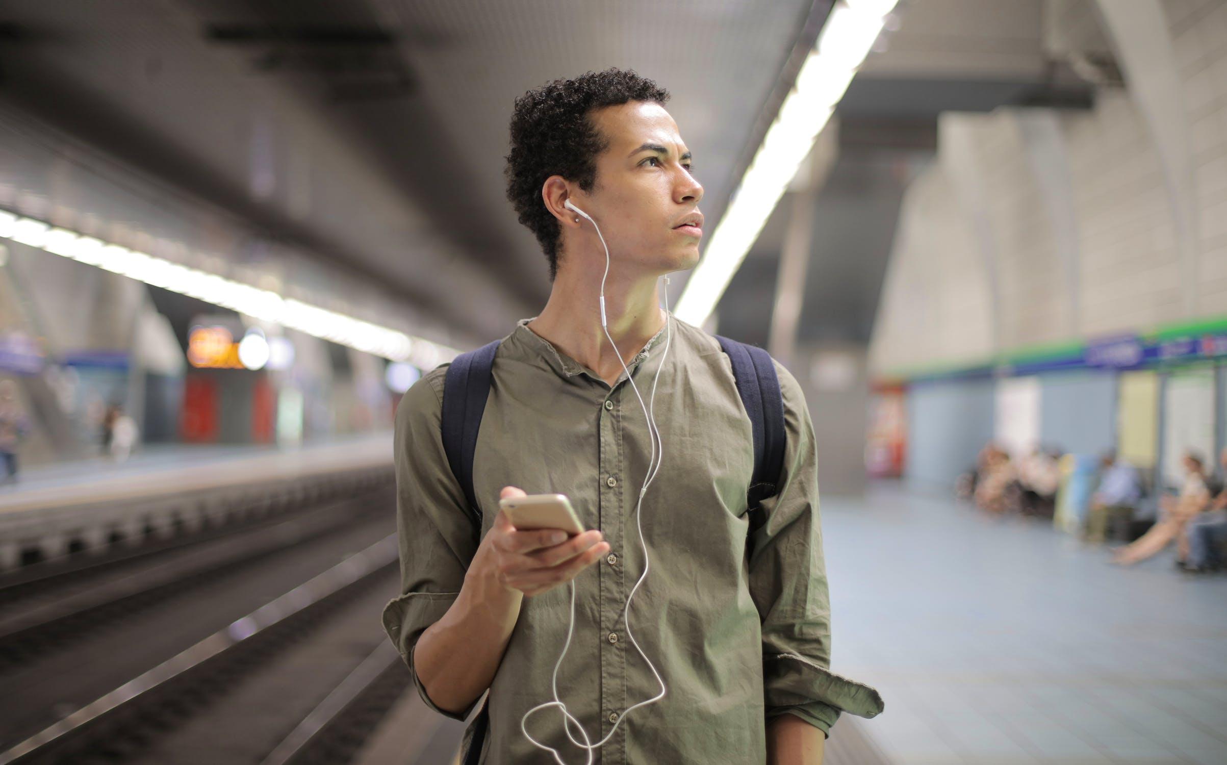 Jongeman die luistert naar muziek op een metrostation